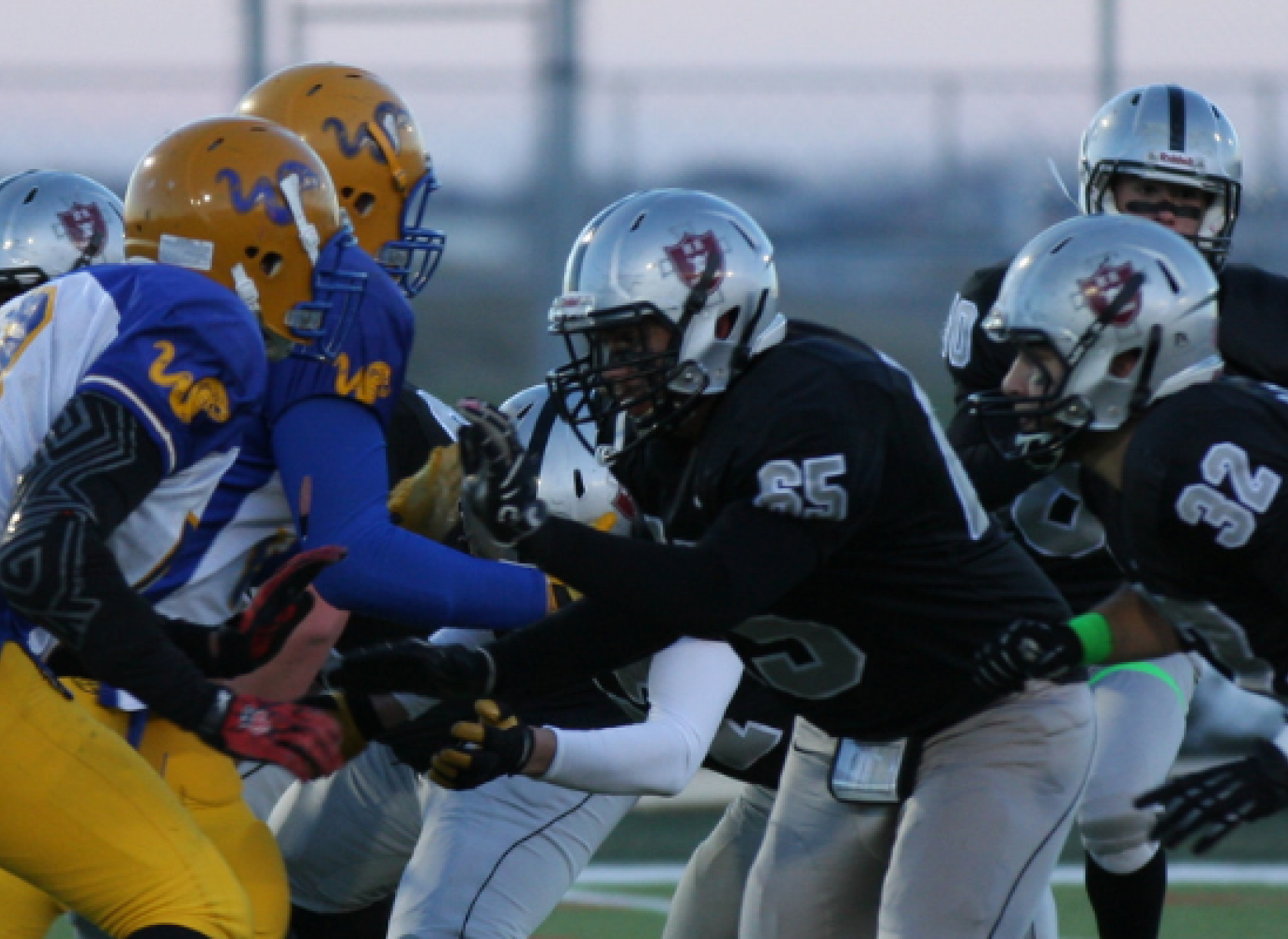 Football offensive and defensive linemen engage at the beginning of a play. The quarterback receives the snap.