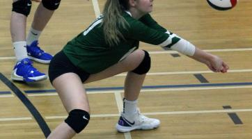 A girl preparing to hit a falling volleyball